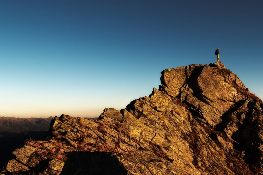Person standing at the top of a mountain